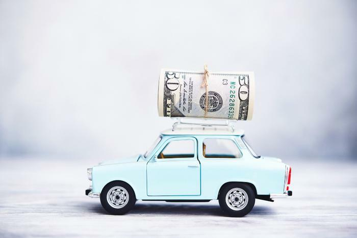 Car prices concept with toy car and money roll on roof