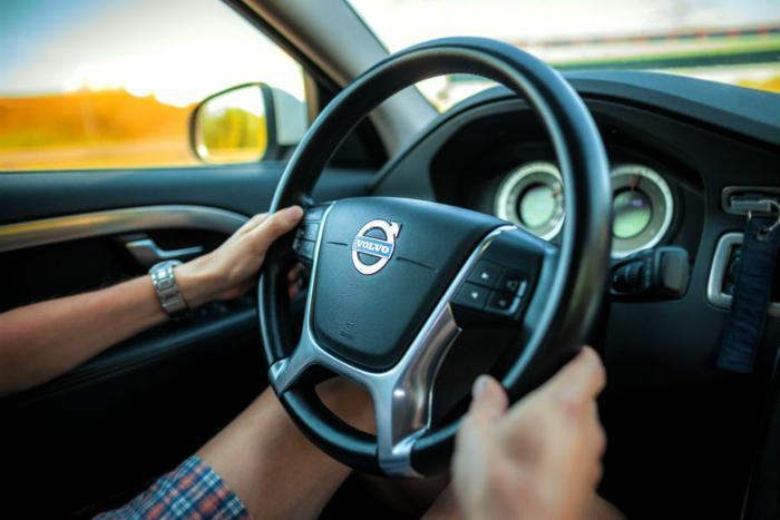 Driver holding Volvo steering wheel