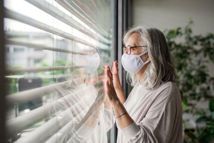 Woman with COVID-19 wearing mask and staring out window