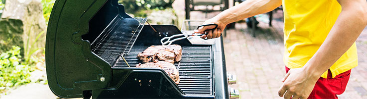man cooking steaks on a grill