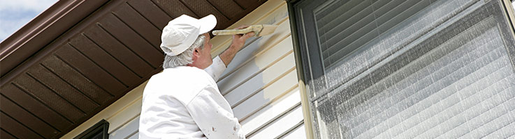 man painting exterior of home