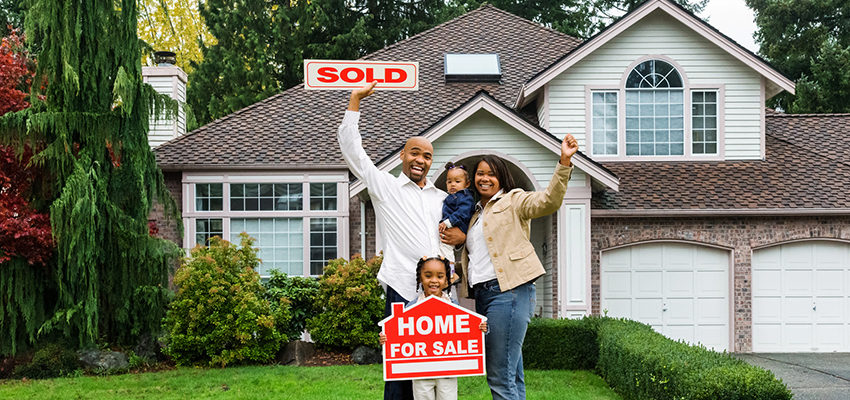 family holding sold home sign