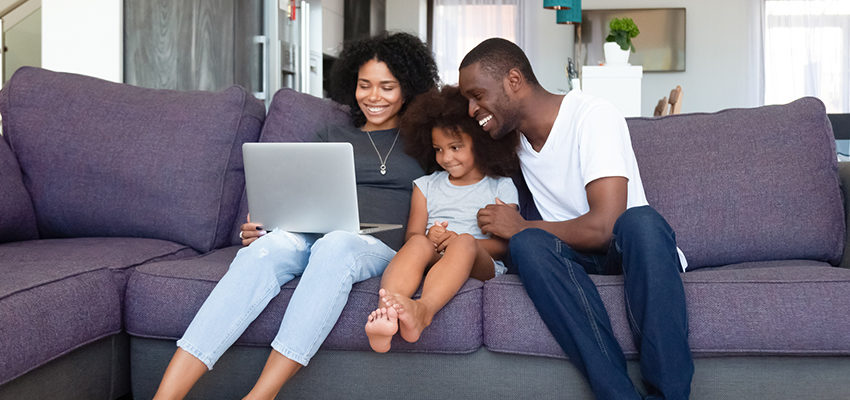 family on couch with laptop