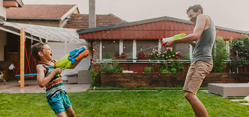 father and son shooting waterguns