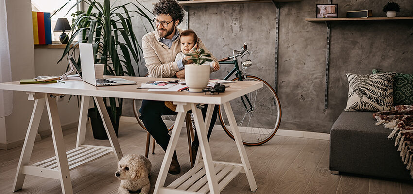 father working in office with baby and dog