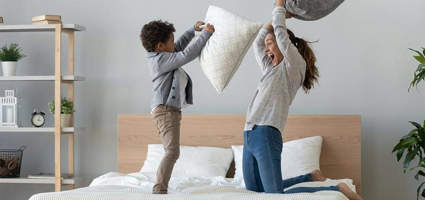 """kid and mom pillow fighting"