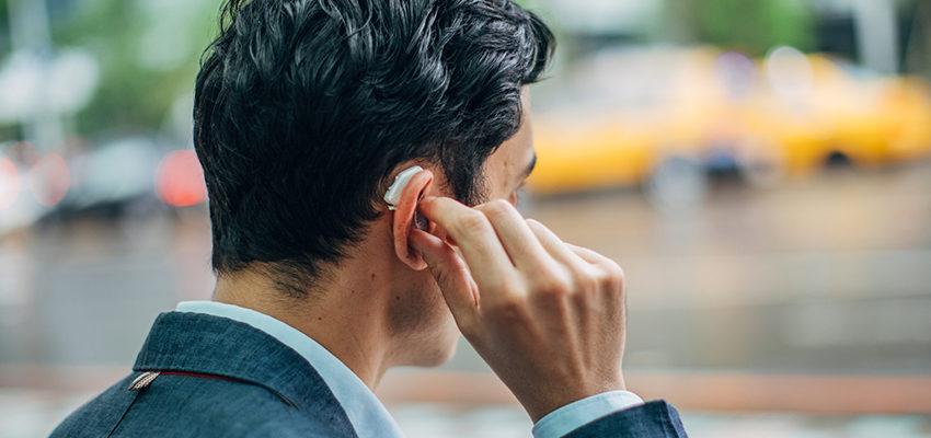 man adjusting hearing aid