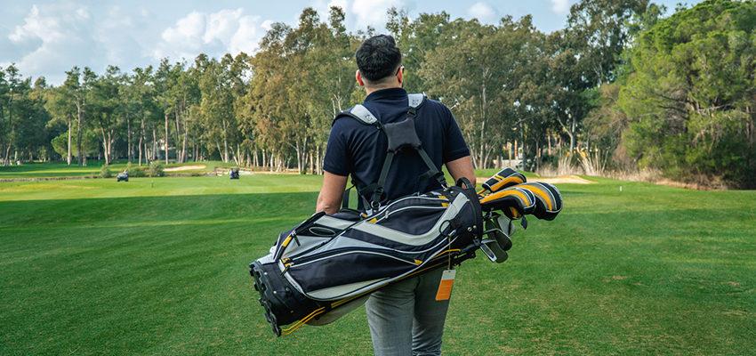 man carrying golf bag