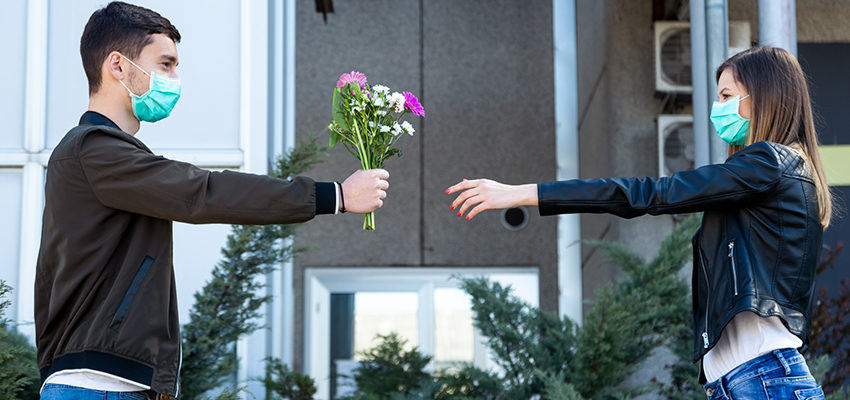 man handing woman flowers