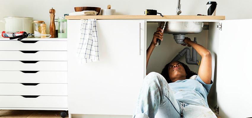 woman fixing sink