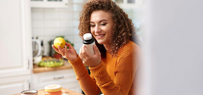 woman holding lemon and vitamins