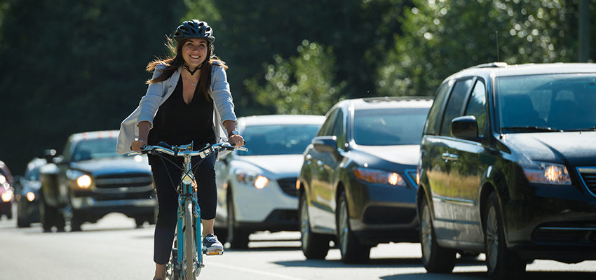 woman riding bike next to traffic